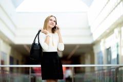 Giovane donna elegante che fa chiamata sul cellulare Immagini Stock