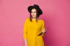 Giovane donna elegante che per mezzo della compressa Fotografia Stock