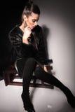 Giovane donna elegante che si siede su un panchetto Fotografie Stock Libere da Diritti