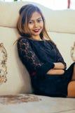 Giovane donna elegante che si siede sul sofà bianco Immagine Stock Libera da Diritti