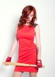 Giovane donna elegante della testarossa in pochi vestito rosso e guanti di cuoio rossi, brandire una mazza da baseball Immagine Stock