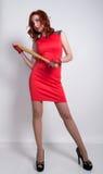 Giovane donna elegante della testarossa in pochi vestito rosso e guanti di cuoio rossi, brandire una mazza da baseball Fotografie Stock Libere da Diritti