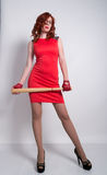 Giovane donna elegante della testarossa in pochi vestito rosso e guanti di cuoio rossi, brandire una mazza da baseball Immagini Stock