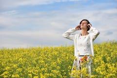 Giovane, donna emozionale e felice che ascolta la musica in cuffie i Fotografia Stock