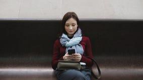 Giovane donna emozionante che manda un sms sullo smartphone che si siede sul banco di marmo in metropolitana archivi video