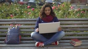 Giovane donna emozionante che si siede sul banco all'aperto e che aspetta i suoi amici archivi video