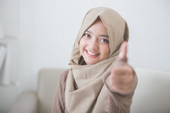 Giovane donna emozionante con hijab che sorride alla macchina fotografica e che mostra Thu Immagini Stock Libere da Diritti