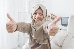 Giovane donna emozionante con hijab che sorride alla macchina fotografica e che mostra Thu Fotografia Stock Libera da Diritti