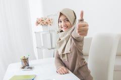 Giovane donna emozionante con hijab che sorride alla macchina fotografica e che mostra Thu Immagine Stock
