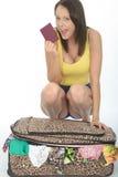 Giovane donna emozionante piacevole felice che si inginocchia dietro una valigia che tiene un passaporto Fotografia Stock