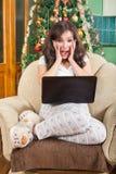 Giovane donna entusiasmata che per mezzo del computer portatile con l'eccitazione Fotografie Stock Libere da Diritti