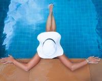 Giovane donna esile in cappello di paglia che si siede nella piscina tropicale Fotografie Stock Libere da Diritti
