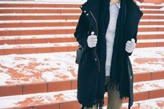 Giovane donna esile in cappotto nero sbottonato, in un maglione grigio ed in guanti fotografie stock libere da diritti
