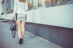 Giovane donna esile che cammina dai tacchi alti d'uso della via fotografia stock libera da diritti