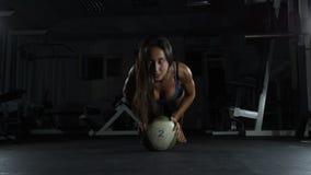 Giovane donna esile che fa una certa ginnastica alla palestra con la palla