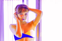 Giovane donna esile che sta nel solarium che ottiene abbronzatura immagine stock libera da diritti