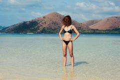 Giovane donna esile che sta sulla spiaggia tropicale Fotografia Stock