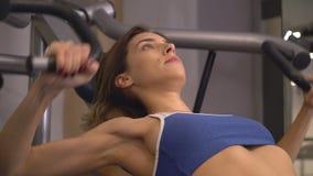 Giovane donna esile del ritratto che risolve i pesi di sollevamento video d archivio