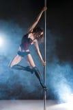 Giovane donna esile di ballo del palo che si esercita sopra il buio Immagini Stock