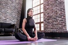 Giovane donna esile sorridente che fa allungando esercizio per le coscie interne che si siedono nella posa di yoga della farfalla Fotografia Stock