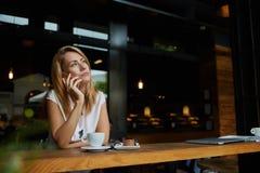 Giovane donna europea affascinante che chiama con il telefono delle cellule durante la prima colazione di mattina in caffetteria, Immagine Stock Libera da Diritti