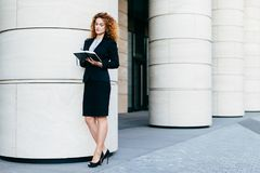 Giovane donna europea con capelli ricci, il costume convenzionale nero d'uso e le scarpe a tacco alto, tenendo il suo diario, scr fotografia stock