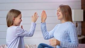 Giovane donna europea sorridente e ragazza sveglia del bambino che giocano le mani d'applauso che si siedono sul letto in camera  archivi video