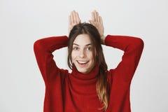 Giovane donna europea sveglia che esamina allegramente la macchina fotografica, tenendo il suoi gesto e sorridere facenti capi di Immagine Stock