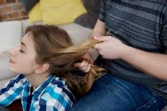 Giovane donna a fare treccia dei capelli fotografia stock