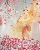 Giovane donna favolosa nella pioggia del petalo fotografie stock libere da diritti