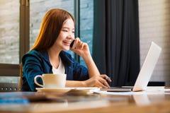 Giovane donna felice in abbigliamento casual che lavora al suo computer e Fotografia Stock Libera da Diritti