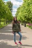 Giovane donna felice in abbigliamento di sport che cammina nel parco di estate fotografia stock libera da diritti