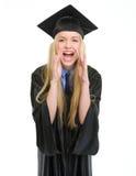 Giovane donna felice nel gridare dell'abito di graduazione Immagini Stock