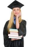 Giovane donna felice in abito di graduazione con i libri Immagini Stock Libere da Diritti
