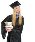 Donna felice in abito di graduazione con la pila di libri Immagine Stock