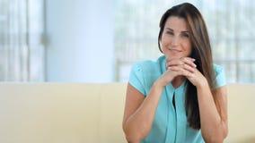 Giovane donna felice alla moda che si siede su un sofà Bellezza, ritratto di modo archivi video