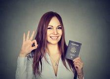 Giovane donna felice attraente con il passaporto di U.S.A. che dà segno giusto Fotografia Stock Libera da Diritti