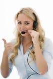 Giovane donna felice attraente di affari che per mezzo di una cuffia avricolare del telefono Fotografie Stock