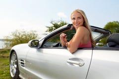 Giovane donna felice in automobile convertibile immagini stock