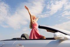 Giovane donna felice in automobile convertibile fotografia stock