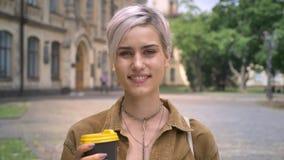 Giovane donna felice bionda con il caffè penetrante della tenuta del naso ed esaminare macchina fotografica, stante sulla via urb video d archivio