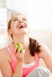 Giovane donna felice in buona salute attraente che tiene mela verde Immagini Stock