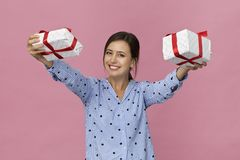 Giovane donna felice in camicia blu elegante con un regalo su fondo rosa Dare un regalo immagini stock