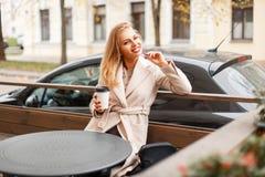 Giovane donna felice in cappotto d'avanguardia con caffè che riposa in un caffè immagine stock libera da diritti