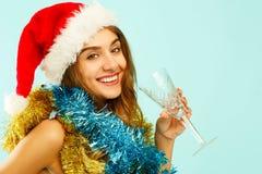 Giovane donna felice in champagne bevente del cappello rosso di Santa Natale Fotografie Stock