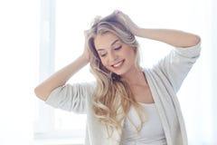 Giovane donna felice che allunga a casa Fotografia Stock
