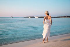 Giovane donna felice che cammina dalla spiaggia Immagine Stock