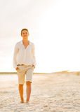 Giovane donna felice che cammina sulla spiaggia alla sera Fotografia Stock