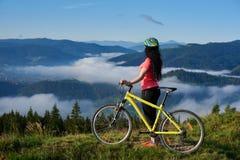 Giovane donna felice che cicla sul mountain bike al giorno di estate fotografia stock