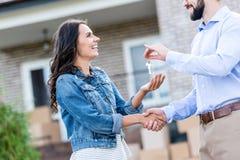giovane donna felice che compra nuova casa e che prende le chiavi fotografia stock libera da diritti